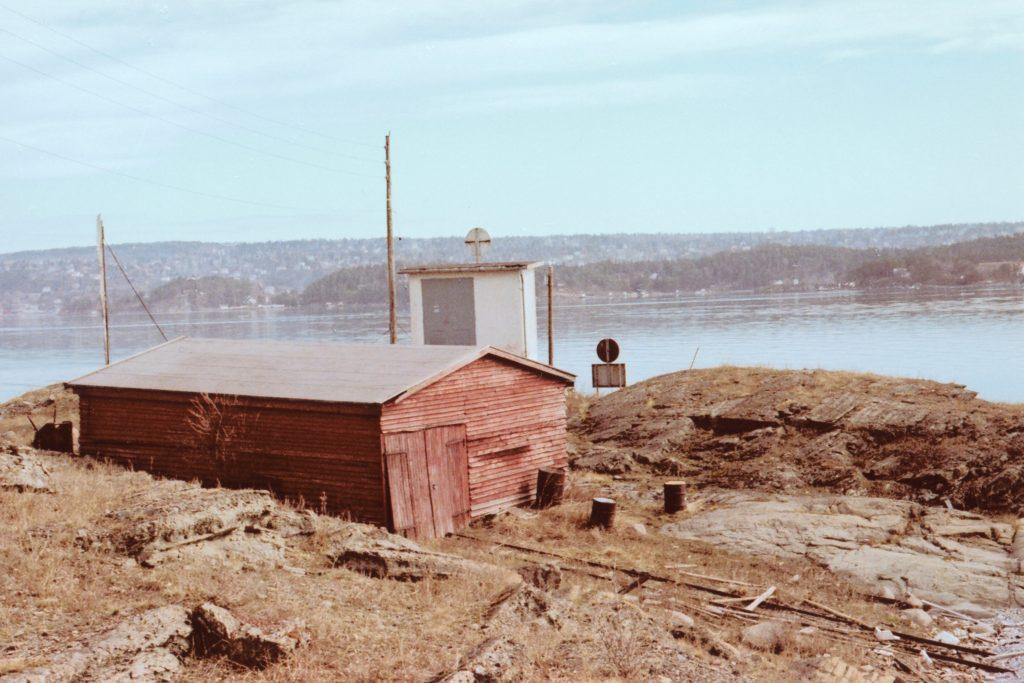 Det gamle båthuset fra 1920-tallet på Kalven. I bakgrunnen transformatorstasjonen oppført i 1950.